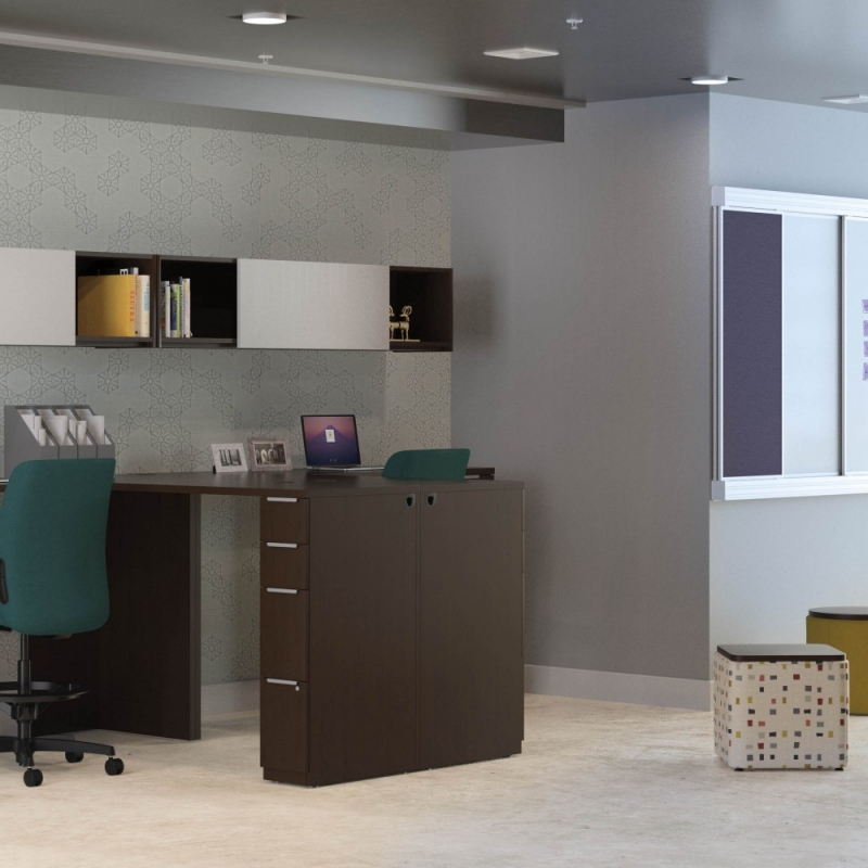 large office space with several desks at bar stool height and with a small seating area next to the desks.