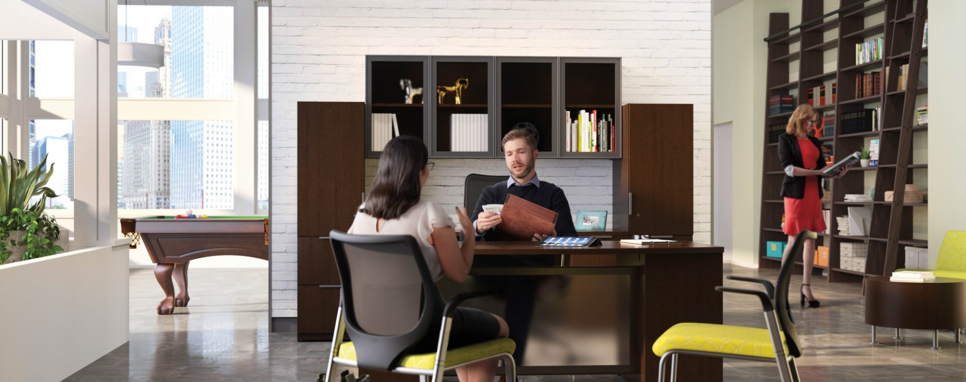 open air office space with a man and woman discussing work at his desk. Yellow stationary high back chairs. Dark wood wall height bookshelves line the walls.