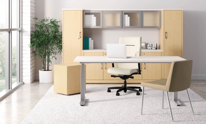 beige room with a beige desk and beige hutch with two closets that has one beige high back wheeling office chair behind the desk and one stationary beige chair in front of the desk