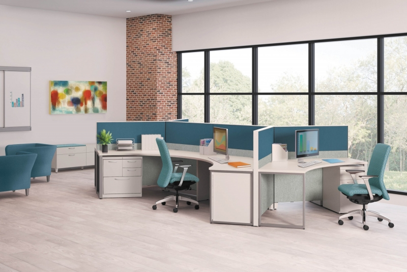 Office table pod with three teal cubicles placed together to for the pod. Each desk is curved and has a filing cabinet and a rolling teal desk chair