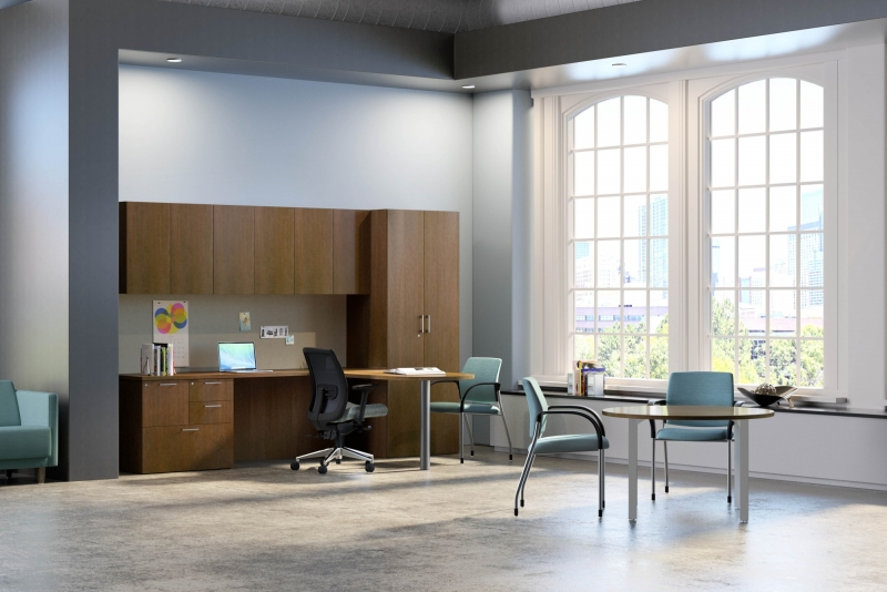 large room in an office with a table that has two blue chairs seated at it as well as a wall of dark brown storage safe cabinets
