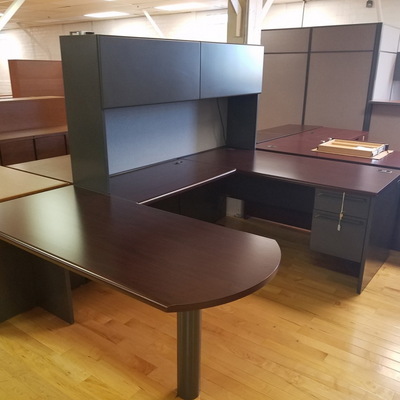 dark brown used desk with a dark brown hutch attached. The desk is shaped like a U.