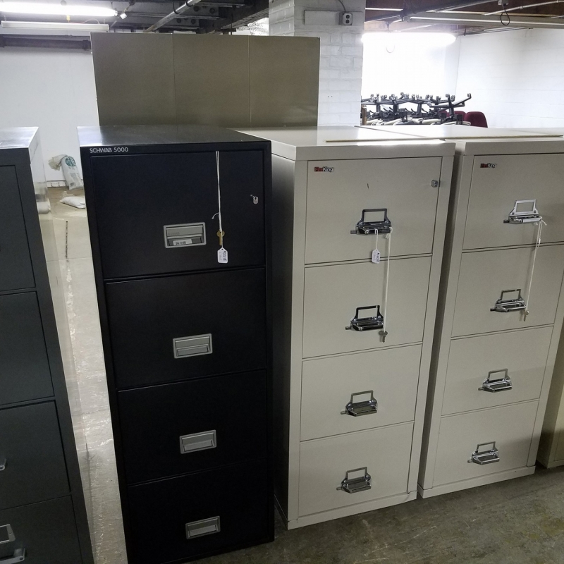 four filing cabinets with three stacked drawers and locked access. Two of the filing cabinets are black and two are tan.
